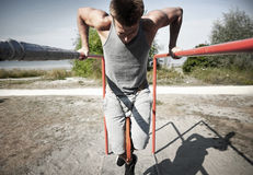 Young man exercising on parallel bars outdoors Stock Photography