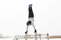 Young man exercising on parallel bars in winter. Fitness, sport, training, people and exercising concept - young man on parallel bars doing handstand outdoors in Royalty Free Stock Photography