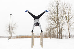 Young man exercising on parallel bars in winter. Fitness, sport, training, people and exercising concept - young man on parallel bars doing handstand outdoors in Stock Images