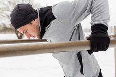 Young man exercising on parallel bars in winter. Fitness, sport, exercising, training and people concept - young man doing triceps dip on parallel bars outdoors Stock Photo
