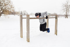 Young man exercising on parallel bars in winter. Fitness, sport, exercising, training and people concept - young man doing triceps dip on parallel bars outdoors royalty free stock photo