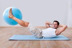 Young man exercising on a pilates ball Royalty Free Stock Photos