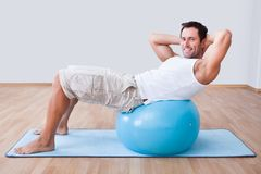 Young Man Exercising On A Pilates Ball Stock Photo