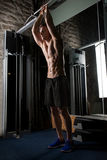 Young man exercising with pull-up bar in gym Stock Images