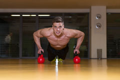 Young Man Exercising Push Ups On Kettle Bell Stock Photos