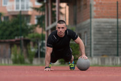 Young Man Exercising Push-Ups On Medicine Ball Outdoor Royalty Free Stock Photo