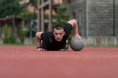 Young Man Exercising Push-Ups On Medicine Ball Outdoor Royalty Free Stock Image