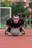 Young Man Exercising Push-Ups On Medicine Ball Outdoor Stock Photography