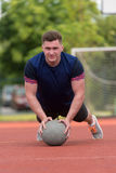 Young Man Exercising Push-Ups On Medicine Ball Outdoor Stock Photo