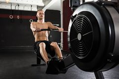Young Man Exercising With Row Machine Stock Image