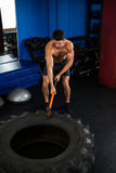 Young man exercising with sledgehammer Royalty Free Stock Images