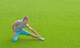 Young man exercising on sports field. Fit young man exercising outdoors on green sports field stock photo