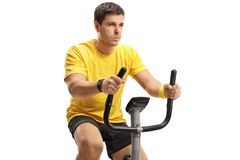 Young man exercising on a stationary bicycle. Isolated on white background Stock Photo