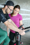 Young man exercising on stationary bikes. Stock Photography
