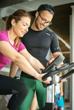 Young man exercising on stationary bikes. Royalty Free Stock Photo