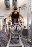 Young man exercising on t-bar row machine in gym Royalty Free Stock Images