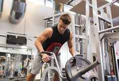 Young man exercising on t-bar row machine in gym Stock Images