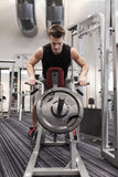 Young man exercising on t-bar row machine in gym Stock Image