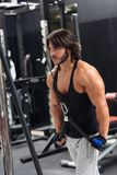 Young man exercising triceps pulldown at the gym. Side view portrait of a determined young man exercising triceps pulldown at cable machine during upper body stock photo