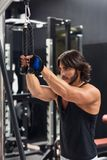 Young man exercising triceps pulldown at the gym. Side view portrait of a determined young man exercising triceps pulldown at cable machine during upper body royalty free stock photography