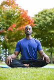 Young man exercising yoga Stock Images