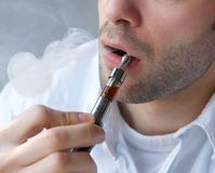 Young man exhaling smoke from electric cigarette. Close up part face of young man exhaling smoke from electric cigarette Stock Photo