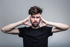 Young man is experiencing intense headache Stock Photos
