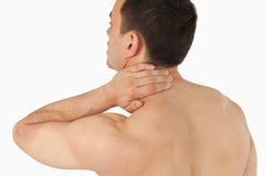 Young man experiencing neck pain. Against a white background Stock Photos