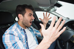 Young man experiencing road rage. In his car Stock Photography