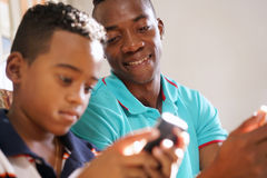 Young Man Explaining Mobile Phone Internet To Boy At Home. Happy black family at home. African american father and child playing game with cell phone. Hispanic Stock Image