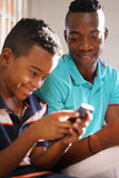 Young Man Explaining Mobile Phone Internet To Son At Home. Happy black family at home. African american father and child playing game with cell phone. Hispanic Royalty Free Stock Photo