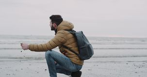 Young man exploring the gray beach after a rain beside of a seashore , closeup capturing video , man taking some wet stock footage