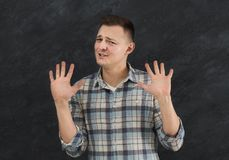 Young man expressing disgust, grimacing. Young man pushing away with his hands in foreground, expressing his refusal, aversion or repulsion with stopping hand Royalty Free Stock Photos