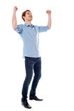 Young man expressing his success. Handsome young man raising his arms in excitement Stock Images