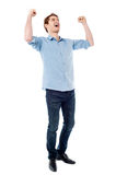 Young man expressing success loudly. Handsome young man raising his arms in excitement Stock Photo