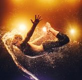 Young man dancing. Young man extreme dancer flying through splashes of water. Vibrant background with warm lights Stock Image