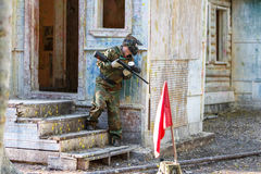 Young man in extreme paintball training with capturing flags. Royalty Free Stock Image