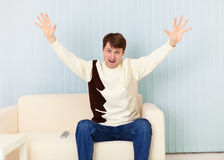 Young man exults sitting on sofa - sports fan Stock Photos