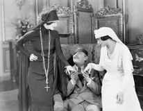 Young man with an eye patch being consoled by a nurse and a religious woman Stock Image