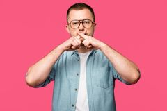 young man in eyeglasses gesturing for silence and holding crossed fingers near lips isolated