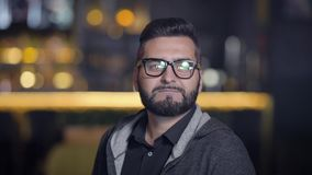Young man in eyeglasses. Young handsome beard guy in casual wear looking away on Bokeh background stock video