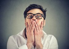 Frightened man in glasses looking at camera. Young man in eyeglasses looking extremely frightened and covering mouth while looking at camera royalty free stock photography