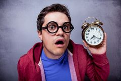 Young man in eyeglasses with metal alarm clock Stock Photo
