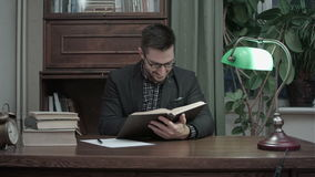 Young man in eyeglasses reading book and smiling to himself stock video