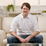 Young man in eyeglasses sitting on sofa at home Royalty Free Stock Photos