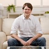 Young man in eyeglasses sitting on sofa at home. Laughing young man in eyeglasses sitting on sofa at home Royalty Free Stock Photos