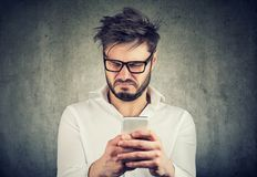Exasperated man watching phone looking disgusted. Young man in eyeglasses surfing social media and looking confused and angry watching news stock photography