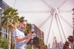 Young man in eyeglasses using his phone in Dubai.  royalty free stock images