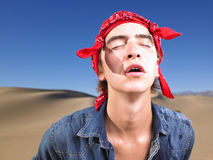 Young Man With Eyes Closed Wearing Bandana. Young man in with eyes closed wearing red bandana. Horizontal shot Royalty Free Stock Photos
