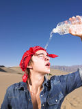 Young Man With Eyes Closed Wearing Bandana. Young man in with eyes closed wearing red bandana pouring water on himself. Vertical shot Stock Photography